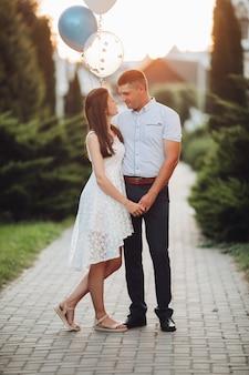 흰 드레스에 긴 검은 물결 모양의 머리를 가진 예쁜 백인 여자가 아름다운 남자와 포옹