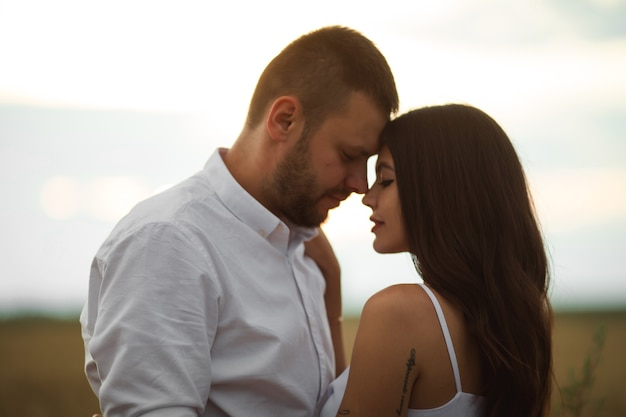 Pretty caucasian woman with long dark wavy hair in white dress hugs with beautiful man in white t-shirt and shorts