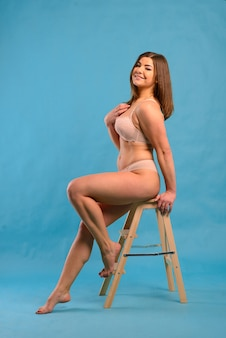 Pretty caucasian woman with plus size body wearing pink lace underwear on a blue studio background