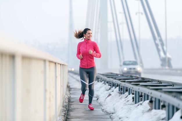 冬の橋の上を実行しているスポーツウェアに身を包んだポニーテールのかなり白人女性。健康的なライフスタイルのコンセプトです。