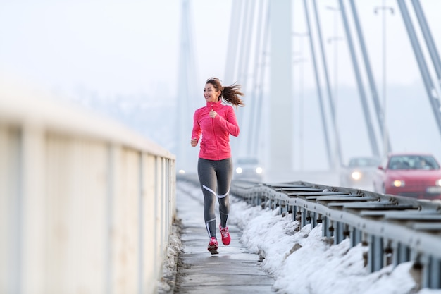 Pretty caucasian woman with ponytail dressed in sportswear running on the bridge at winter. healthy lifestyle concept.