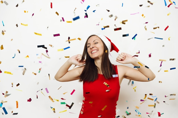 Pretty caucasian young happy woman with healthy skin and charming smile wearing red dress and christmas hat holding hands on head isolated on white background. santa girl. new year holiday 2018.