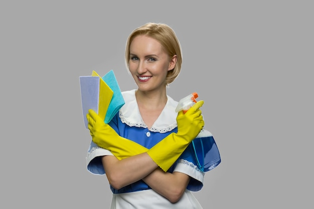 Pretty chambermaid holding cleaning spray and rags. young beautiful woman maid holding cleaning supplies and looking at camera.