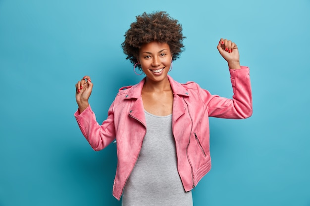 Pretty charming afro american woman spends great time with friends, dances carefree, keeps hands raised, chills indoor, catches rhythm of music, wears fashionable clothes,