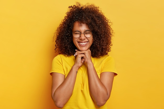 Pretty charming afro girl with curly hair, rejoices life, keeps hands under chin, feels overjoyed and satisfied, has natural appearance, wears bright yellow t shirt, poses indoor. happiness concept