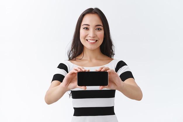ストライプのtシャツを着たかなり魅力的なアジアの女性、スマートフォンを水平に持ち、ゲームやアプリケーションを紹介するように笑って、ダウンロードして使用するのに良いアプリをお勧めします、白い背景に立つ