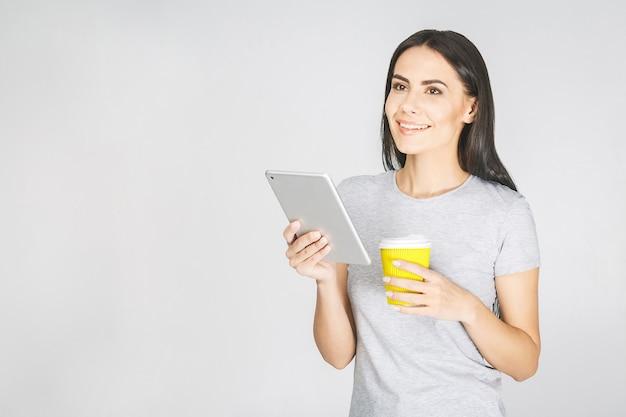 Довольно очаровательная уверенная модная женщина в повседневной одежде с планшетом в руках и пьет кофе
