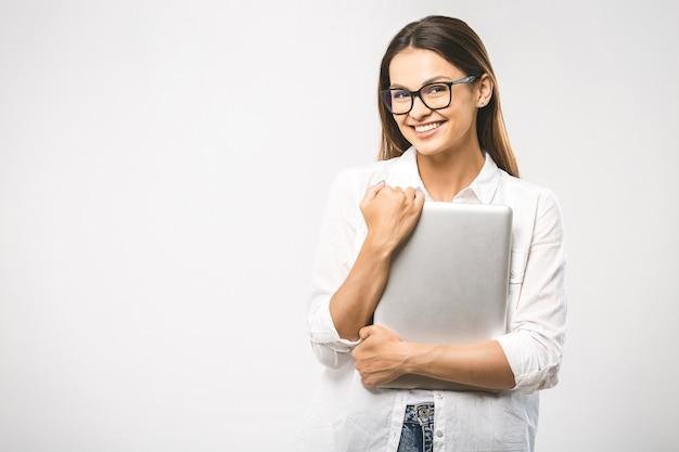 手にタブレットを持っている古典的なシャツのかなり魅力的な自信を持ってトレンディな女性