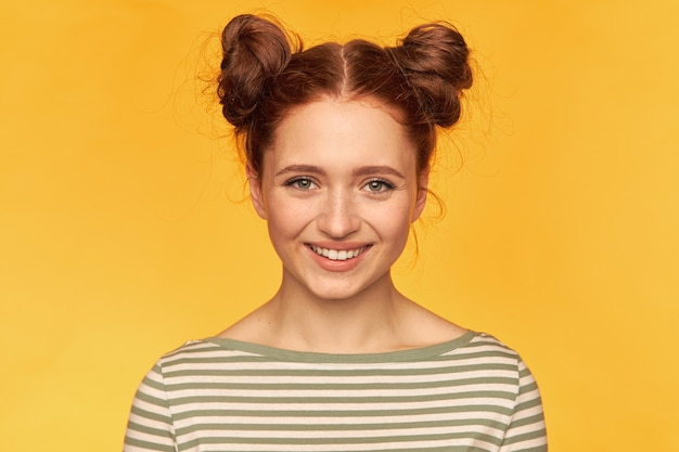 Pretty, charming ginger woman with two buns and healthy skin. feels happiness. wearing striped sweater