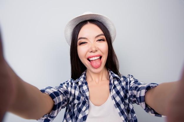 Довольно очаровательная девушка в повседневной одежде и шляпе делает селфи