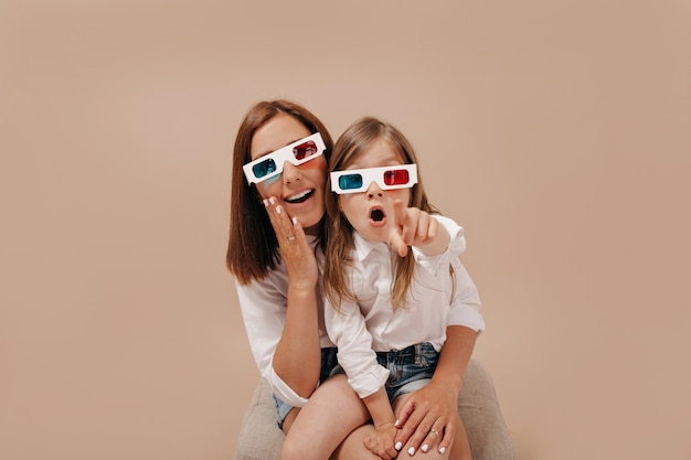 Pretty charming little girl with mom watching a movie in 3d glasses and showing a point to camera