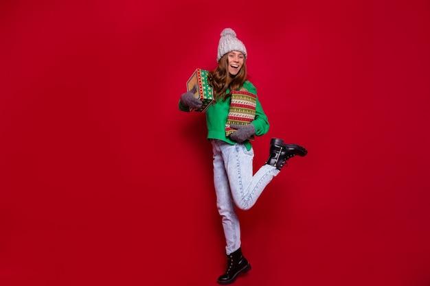 겨울 옷에 붉은 벽에 포즈 크리스마스 선물 상자와 꽤 매력적인 젊은 여자