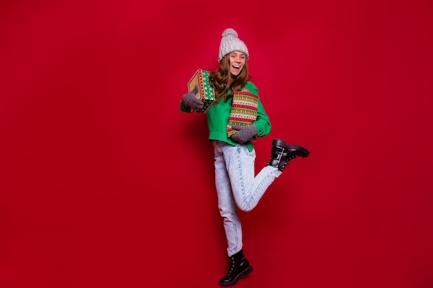 Pretty charming young woman with christmas gift box posing on red wall in winter outfit