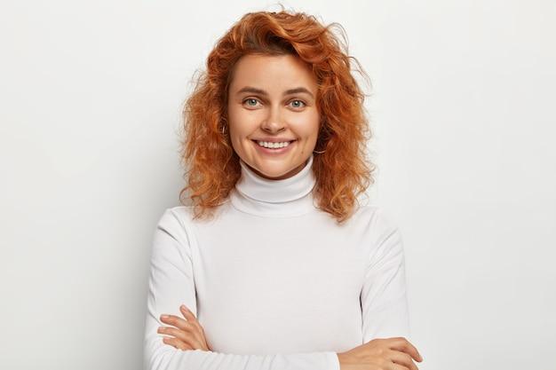Довольно очаровательная молодая женщина с короткими рыжими волосами, идеальными белыми зубами и здоровой чистой кожей, держит руки скрещенными, получает хорошие новости, смотрит прямо, изолирована на белой стене