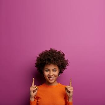 かなり陽気なアフリカ系アメリカ人の女の子があなたを二階に招待し、上記の製品とポイントをお勧めし、幸せな表情をし、紫色の壁に隔離されたカジュアルなオレンジ色のジャンパーを着て、喜びで見つめます