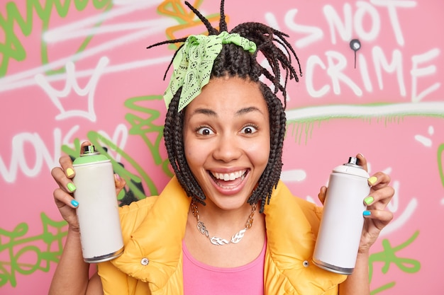 Pretty cheerful afro american hipster girl with dreadlocks smiles broadly holds two aerosol bottles feels happy and positive uses aerosol sprays for drawing graffiti