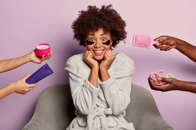Donna afroamericana piuttosto allegra con macchie di idrogel sotto gli occhi per ridurre i puffini