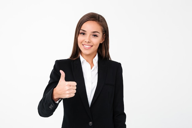 Pretty cheerful business woman showing thumbs up
