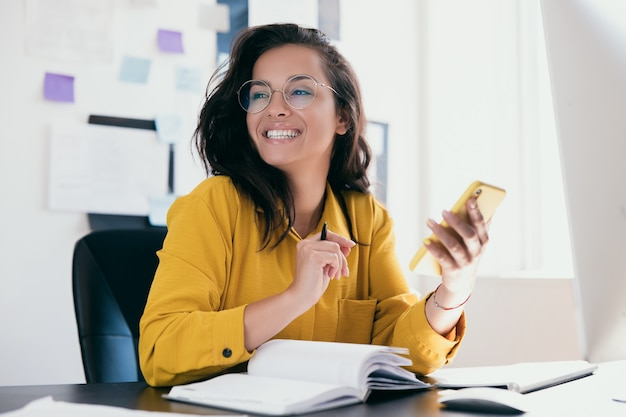 Pretty cheerful businesswoman looking away sitting at desk and holding phone in hand