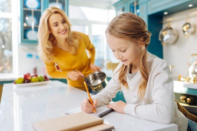 Довольно жизнерадостная белокурая школьница улыбается и пишет в блокноте, пока ее мать стоит рядом с ней с кастрюлькой