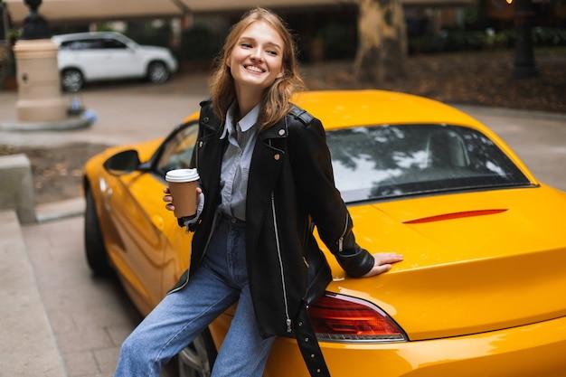 행복 하 게 손에가 서 커피 한잔 들고 노란색 스포츠 자동차에 기대어 가죽 재킷에 꽤 명랑 소녀