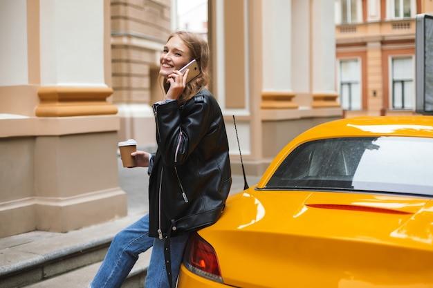 Довольно жизнерадостная девушка в кожаной куртке с чашкой кофе, чтобы пойти, опираясь на желтый спортивный автомобиль, радостно разговаривая по мобильному телефону