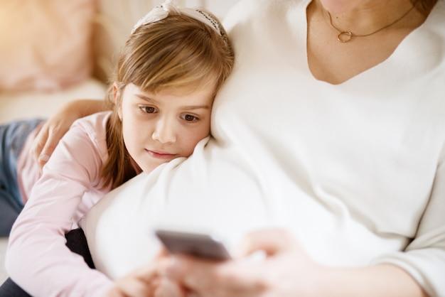 携帯電話を使用しながら妊娠中の母親の腹の上に横たわるかなり陽気な幼児の女の子。家族と新しい生活のコンセプト。