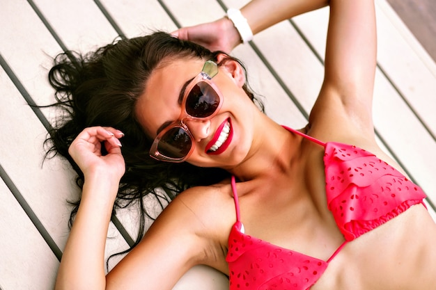 Pretty cheerful positive brunette woman smiling and laughing, having great time alone, laying at wooden floor near pool, week to bikini and sunglasses, vacation holidays time.