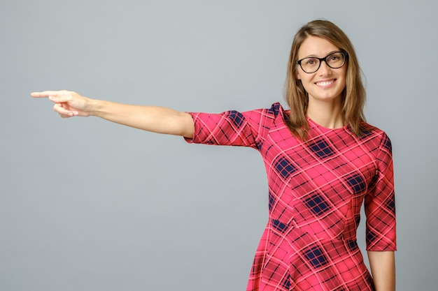 Pretty cheerful woman gesturing with fingers and hand and showing away