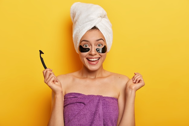 La donna abbastanza allegra ha la pelle pura, sta avvolta in un asciugamano, tiene in mano la lama del rasoio, si prepara per la rasatura, ha trattamenti igienici, sembra rinfrescata, sorride delicatamente