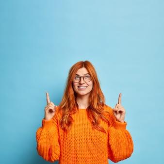 かなり陽気な女性はコピースペースで頭上を指している赤い髪をしています