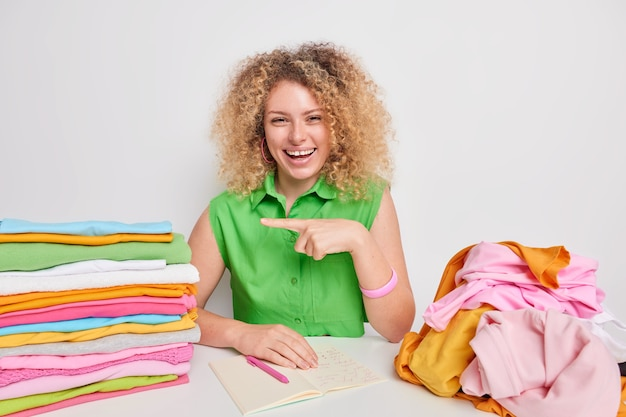 Pretty cheerful woman with curly hair talks about whitener for laundry takes useful notes about washing temperature and wash cycle poses at table near piles of folded clothing isolated on white wall