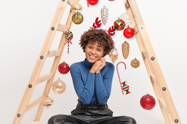 Pretty cheerful woman with curly hair tilts head and smiles happily dressed in casual clothes poses on floor with ladder to decorate room going to celebrate new year spends leisure time at home
