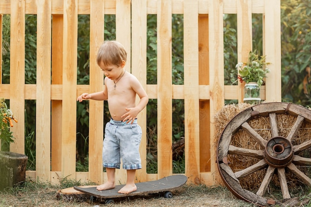 Довольно веселый мальчик милый ребенок катается на скейтборде на открытом воздухе