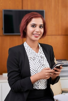 Pretty cheerful young businesswoman standing in office and answering text messages of colleagues and clients