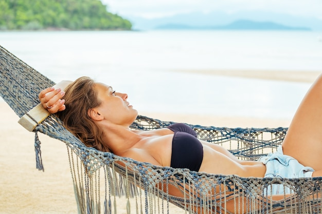 Pretty cheerful young girl lying in a hammock on the beach and smiling in a black bikini and sunglasses