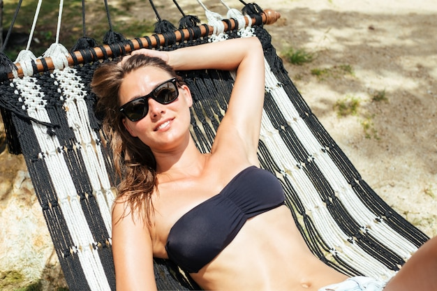 Pretty cheerful young girl lying in a hammock on the beach