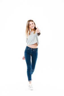 Pretty cheerful young woman standing and showing thumbs up gesture