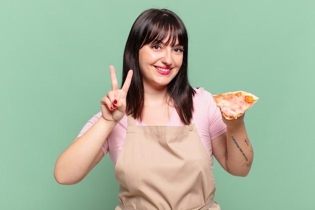 성공적인 승리를 축하하고 피자를 들고 예쁜 요리사 여자