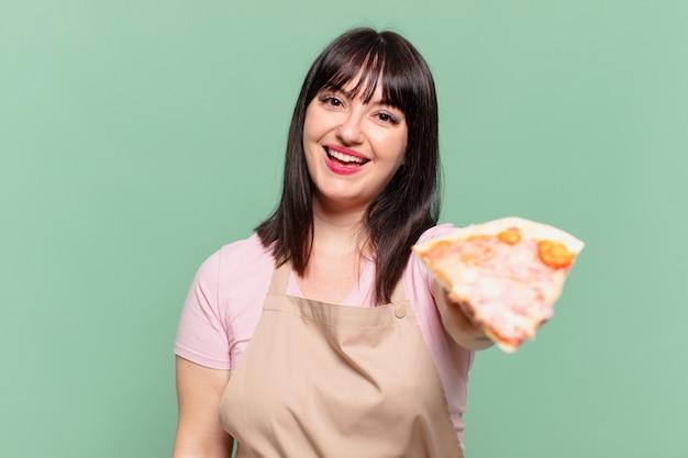 かわいいシェフの女性の幸せな表情とピザを持っています