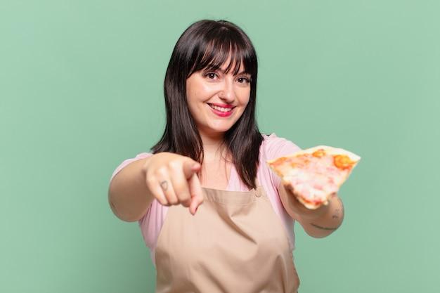 예쁜 요리사 여자 가리키는 또는 표시 및 피자를 들고