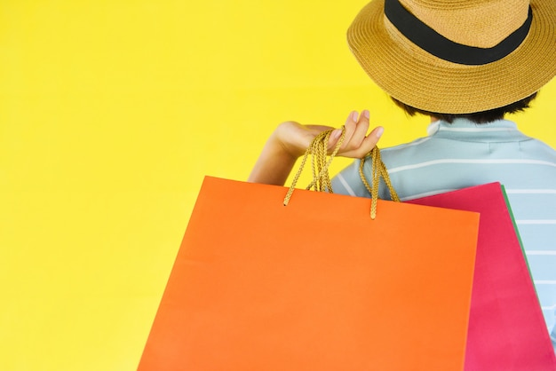 Pretty child girl hands holding shopping bag on yellow