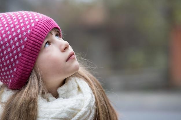 屋外で暖かいニットの冬服を着たかわいい子の女の子。