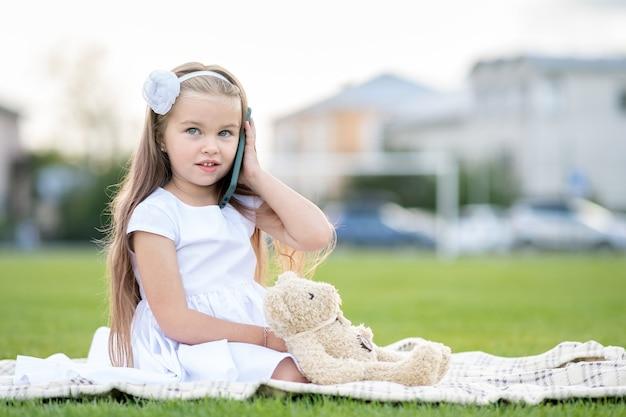 夏の屋外で携帯電話で話している彼女のテディベアのおもちゃと緑の芝生の芝生の上の夏の公園に座っているかわいい子の女の子。