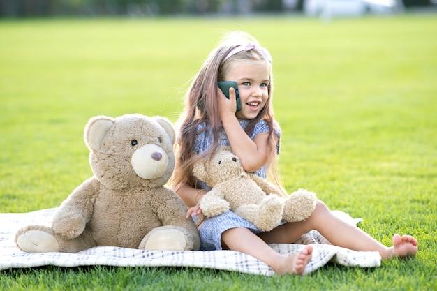 Симпатичная детская девочка, сидящая в летнем парке на зеленой лужайке с игрушкой плюшевого мишки, разговаривает по мобильному телефону на открытом воздухе летом.