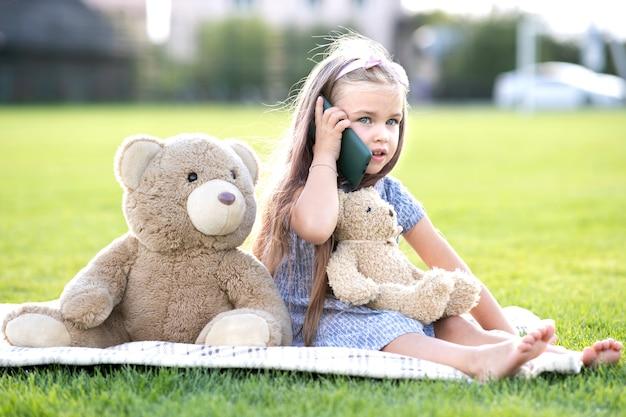 緑の芝生の上の夏の公園に座っているかわいい子供の女の子は、夏の屋外で幸せに笑っている携帯電話で話している彼女のテディベアのおもちゃと一緒に。