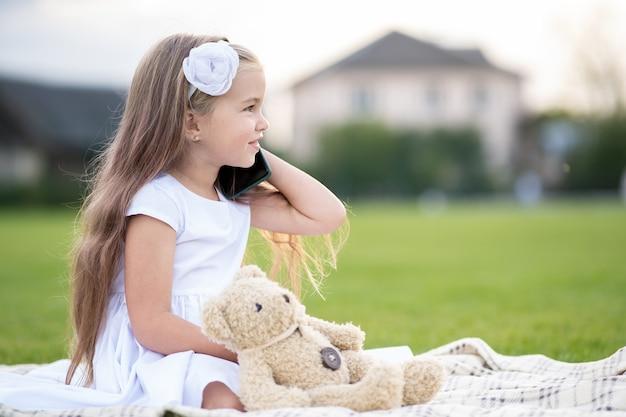 夏の屋外でテディベアのおもちゃが携帯電話で話している緑の芝生の上の夏の公園に座っているかわいい子の女の子。