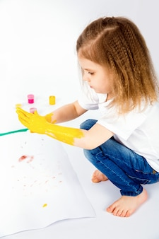 Pretty child girl smears yellow paint on hands