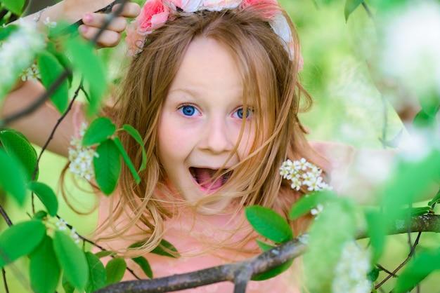 かわいい子の女の子の笑顔と庭、咲く木、チェリー、リンゴの花で遊んで。