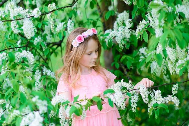 Симпатичная детская девочка улыбается и играет в цветах сада